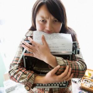 Woman holding typewriter.